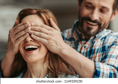 Who is it. Happy man closing eyes of lady with attractive smile with hands