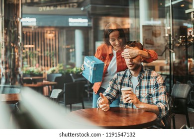 Who is it. Portrait of optimistic woman closing eyes of astonished man while keeping gift for him in arm. He drinking mug of appetizing liquid at desk in cafe