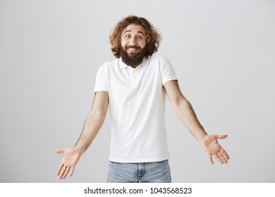Who knew about consequences. Portrait of clueless carefree eastern male with beard and curly hair, smiling awkwardly and shrugging with spread palms, being confused and unaware of anything