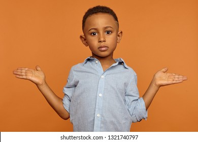 Who knows, so what. Indifferent or confused black schoolboy standing against orange wall background, gesturing emotionally, doesnn't know answer while being interrogated at lesson by teacher
