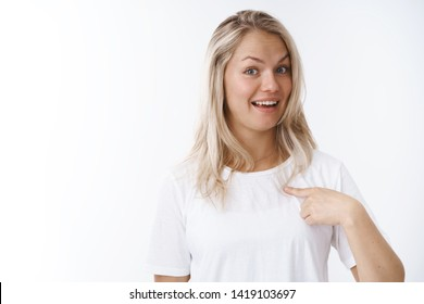 Who me. Portrait of surprised young attractive charismatic positive woman with blond hair in white t-shirt raising eyebrows in surprise smiling delighted pointing herself, being picked