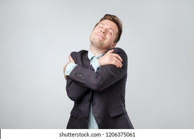 Who need girlfriends if you can hug yourself. Funny playful european guy in suit cuddling himself and smiling from pleasure, closing eyes and dreaming