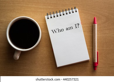 Who am I? A question in handwriting on a notebook with cup of coffee