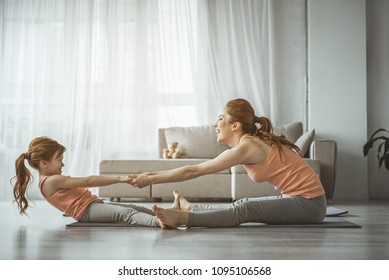 Who is stronger. Full length portrait of little girl trying to outweigh her mom during sport exercise on the floor. Both looking very happy and smile