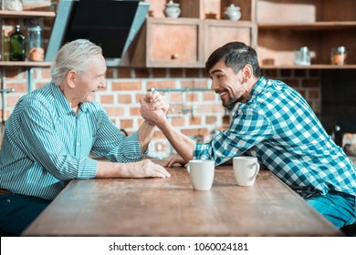 Who is stronger. Nice happy positive father and son sitting opposite each other and playing arm wrestling while deciding who is stronger
