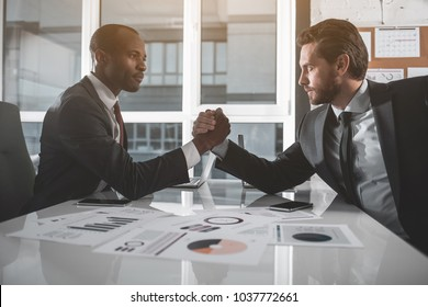 Who is stronger. Side view profile of two managers are sitting opposite each other with one elbow resting on table, clasp each other's hands, and trying to force each other's arm down onto the desk