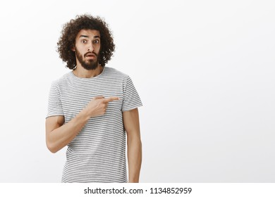 Who is that. Questioned unaware man interested in item, pointing right with index finger and gazing with clueless intrigued expression at camera, asking questiong about product over gray wall