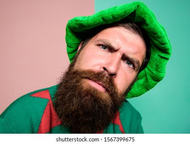 Who is there. Picky man looking at camera. Bearded elf. Winter carnival. St Patricks day. Hipster with beard wearing green costume for party. Christmas elf. Elf concept. Traditions or customs.