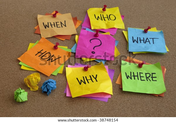 who, what, where, when, why, how questions - uncertainty, brainstorming or decision making concept, colorful crumpled sticky notes on cork bulletin board