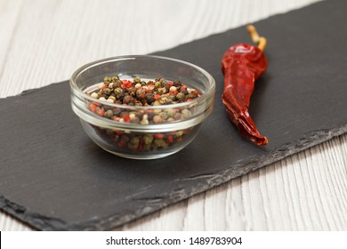 Whole allspice berries in glass bowl and dry red pepper on stone cutting board and wooden table. Shallow depth of field. Focus on allspice berries and pepper..