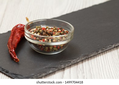 Whole allspice berries in a glass bowl and a dry red pepper on stone cutting board and wooden table. Shallow depth of field. Focus on allspice berries and pepper..