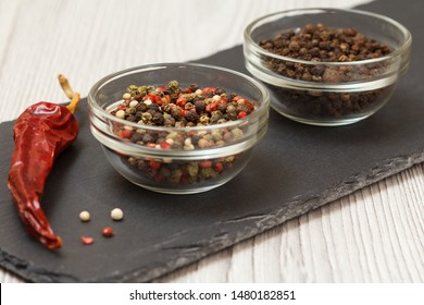 Whole allspice berries in glass bowls and dry red pepper on stone cutting board and wooden table. Shallow depth of field. Focus on allspice berries.