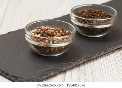 Whole allspice berries in glass bowls on stone cutting board and wooden table. Shallow depth of field. Focus on allspice berries.