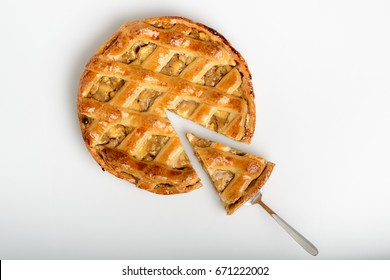 Whole apple pie, top view, a piece is taken out with a chrome cake server