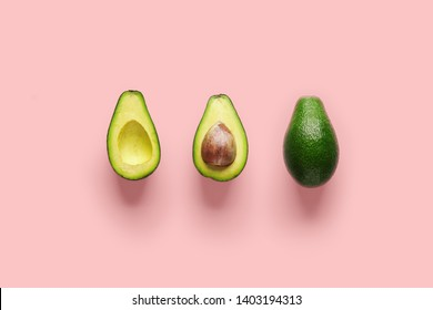 Whole avocado fruit and two halves in a row isolated on pink background. Green avocadoes, minimal flat lay style.