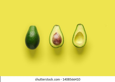 Whole avocado fruit and two halves in a row isolated on yellow background. Green avocadoes, minimal flat lay style.