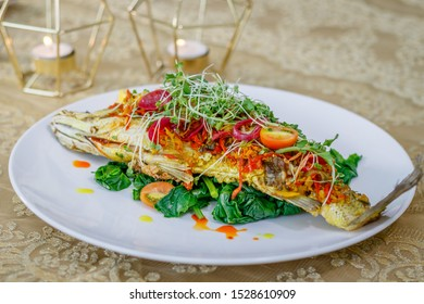 Whole Baby Barramundi with Kai-lan (Chinese broccoli), Chilli, Ginger, Turmeric, Coriander and Lemon. Decorated with onion colored with beetroot juice and green sprouts. Side view.