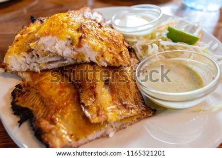 Whole baked or Grilled sole fish fillet with lemon on white plate isolated on a white plate with wooden textured background