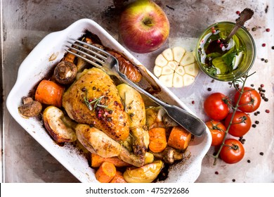 Whole baked juicy chicken with golden crispy skin. Roasted chicken in baking dish with apples, carrot, mushrooms, rosemary, garlic, pepper on rustic iron oven-tray. Overhead. Dinner. Cooked poultry