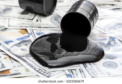 Whole barrel of oil and crude oil spilled from barrel on the dollar bills.