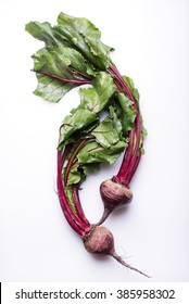 whole beetroots with green leaves, isolated on a white background, top view, vertical