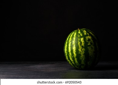 A whole big watermelon on a black table background. Green, hard and striped watermelon. Cold and sweet summer snacks. Copy space.