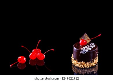 A whole black forest cake with cherry on black background. Space for text