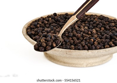 Whole Black Pepper in Old stone bowl and on Spoon