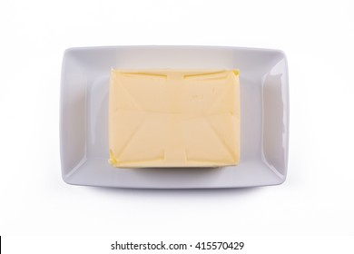whole block butter on white plate isolated on white background, top view