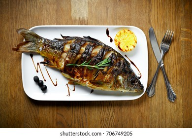 Whole body grill roasted carp fish dish with rosemary and lemon on a white plate on a wooden table in a restaurant