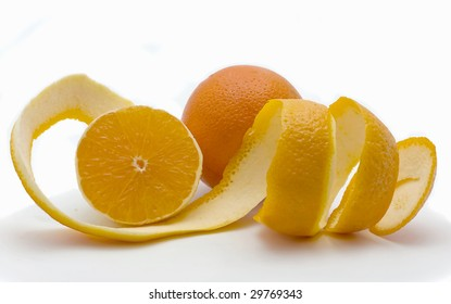 Whole both half of orange and a peel in the form of a spiral on a white background