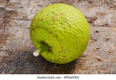 a whole breadfruit on a wooden background