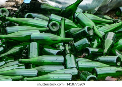 whole and broken green bottles, lie a mountain on the pavement. Concept: waste recycling, disposal of garbage and glass objects.