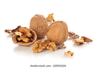 Whole and broken walnuts isolated on white background.