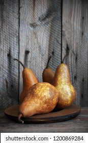 Whole brown pears on rustic wood table against barn wall.