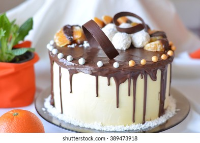 Whole cake decorated with chocolate stripes and mandarin pieces