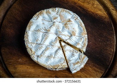 Whole camembert cheese on rustic wooden cutting board , top view