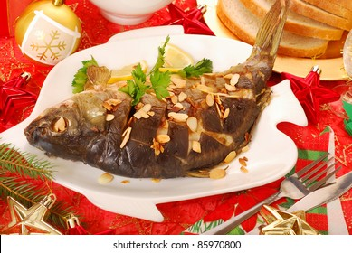 whole carp baked with flaked almonds on christmas table
