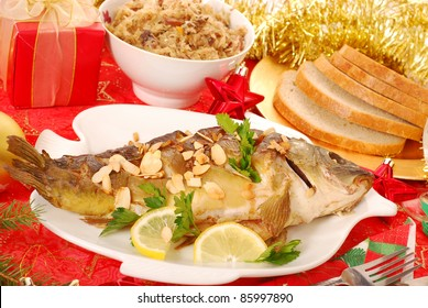 whole carp baked with flaked almonds served with sauerkraut (bigos) and bread on  christmas table