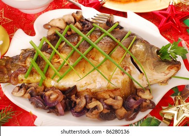 whole carp baked with mushrooms and red onion  and chives decoration  on  christmas table