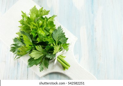 whole celery on a white cutting board on a blue table