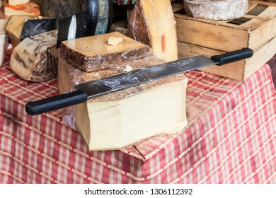 Whole cheese with large two handed slicing knife on top.  On a red and white check cloth