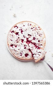 Whole cherry cake with almond petals and sugar powder on white background with cherry flowers. Top view.