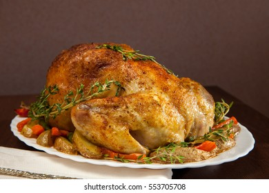 Whole chicken baked with vegetables and thyme