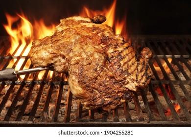 Ganzes Hühnergegrillt auf heißem Barbecue Charcoal Flaming Grill. Juicy Hühnerfleisch am Grill geröstet. Grillpartys im Hinterhof aus Geflügel einzeln auf schwarzem Hintergrund, Nahaufnahme.