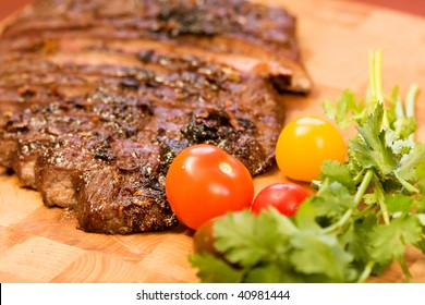 Whole Chipotle Grilled Flank steak on wood cutting board