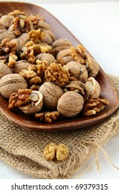 whole and chopped walnuts on a brown background