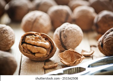 Whole and chopped walnuts on old wooden table