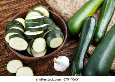 Whole and chopped zucchini on the kitchen table, next to the head of garlic