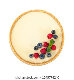 Whole classic cheesecake with raspberries, blueberries and mint isolated on white background. Top view.